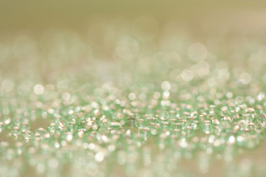 Worker Beads – Thumbnail of a texture of pale green glass beads & reflected bokeh bubbles